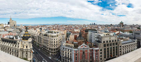 Panorama view of Gran Vía and Madrid's skyline on a cloudy Spring early morning, with the Metropolis building to be recognized in the foreground. Some other landmarks like the Telefonica skyscraper, Faro de Moncloa, Colon Tower or AZCA skyscrapers are al