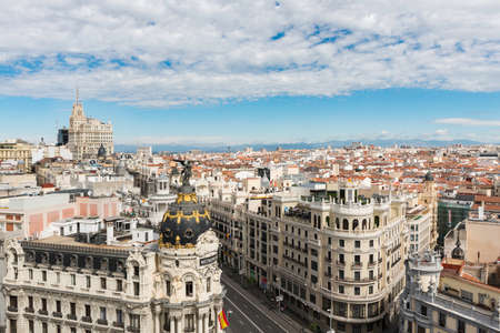 Aerial view of Gran Vía and Madrid's skyline on a Summer early morning, with the Metropolis building to be recognized in the foreground. Some other landmarks like the Telefonica Building to Faro de Moncloa are also to be recognised.