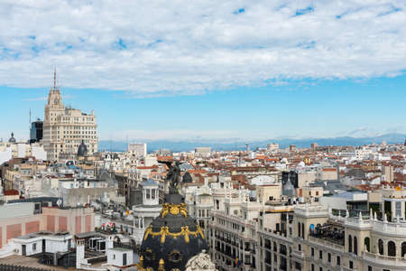 Aerial view of Gran Vía and Madrid's skyline on a Summer early morning, with the Metropolis building to be recognized in the foreground. Some other landmarks like the Telefonica Building and Faro de Moncloa are also to be recognised.