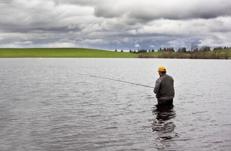 Angler fishing for pikes in a small lake