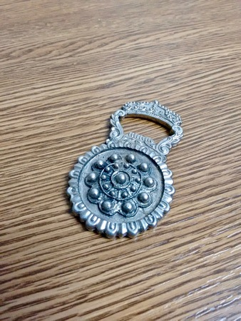 Silver colored bottle opener from Salamanca on top of a table