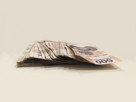 A pile of 500 pesos mexican bank notes over a white desk Banco de Imagens