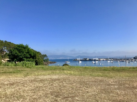 View of a field with trees near the beach and the sea during a beautiful sunny summer day in Sanxenxo Galicia Spain