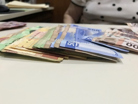 Many mexican pesos bills spread over a beige colored desk inside a small business office Banco de Imagens