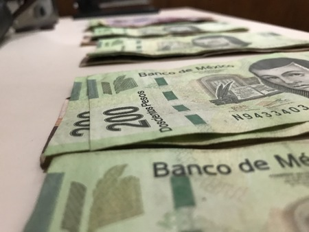 Some mexican pesos bills spread over a beige desk inside a small business office