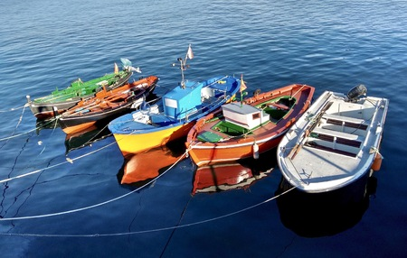 Colorful fishing boats docked during summer in O Grove Spain on a nice sunny day Banco de Imagens