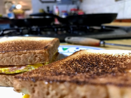 Ham omelette sandwich on foreground and kitchen in the background Фото со стока