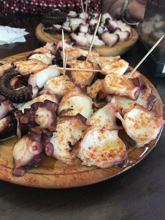 A wooden plate with a helping of pulpo a feira style boiled octopus Stock Photo