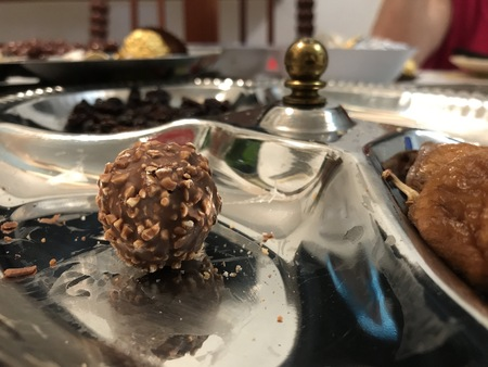 Stainless steel tray with chocolate ball, figs and raisins during Christmas dinner.