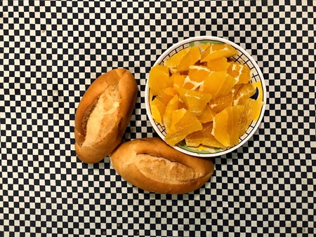 Top view of a bowl of chopped oranges with two french dinner bread