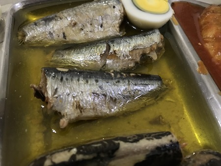 Cooked egg cut in halves, sardines and tuna on a stainless steel tray placed on a blue checkered tablecloth Stock Photo