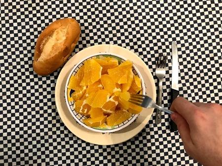 Top view of a bowl of chopped oranges with one piece of bread at the left