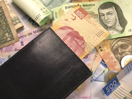 Many mexican pesos and other latin american money bills spread over a wooden desk inside a small business office Banco de Imagens