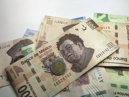 Many mixed mexican peso bills over a white background Banco de Imagens