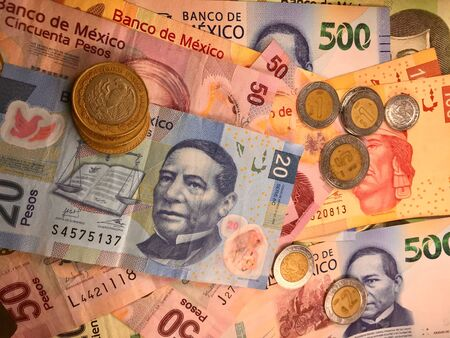 Many mexican pesos bills spread randomly over a flat surface