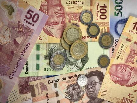 Viele mexikanische Pesos-Scheine verteilen sich zufällig auf einer ebenen Fläche Standard-Bild