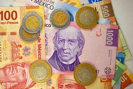 Many mexican pesos bills spread randomly over a flat surface