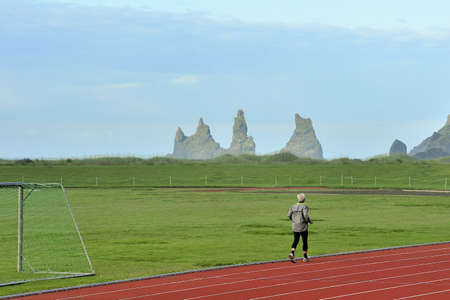 a man jogging at the stadium of Vik, Iceland on the backgroung of Reynisdrangar Rocks photo