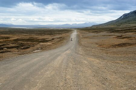 a biker traveling on a dirt road of Iceland photo