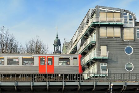 jahr: HAMBURG, GERMANY - MARCH 18, 2015: train and Headquarters of the Gruner Jahr Publishing from the Elbe side near Saint Michaelis Church. Gruner Jahr GmbH is the largest European printing and publishing company.