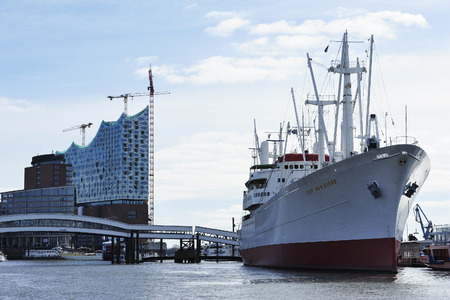sued: HAMBURG, GERMANY -22 MARCH 2015: Construction of the Elbe Philharmonic building behind the museum cargo ship MS Cap San Diego.The Cap San Diego was built and launched by Deutsche Werft in 1961 for Hamburg Sued.
