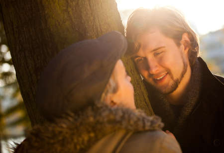 Romantic couple about to kiss behind a tree   photo