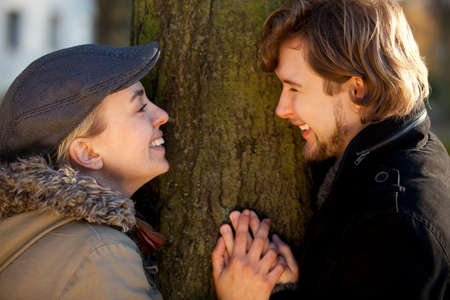 Portrait of a romantic couple outdoors behind a tree  photo