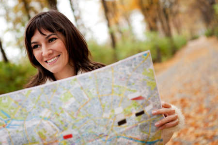 Woman sightseeing outdoors and holding a map   photo