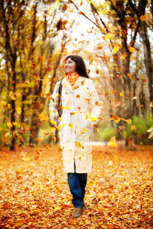Autumn woman walking outdoors and leaves falling on her  photo