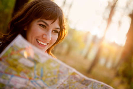 explore: female explorer looking at a map outdoors Stock Photo