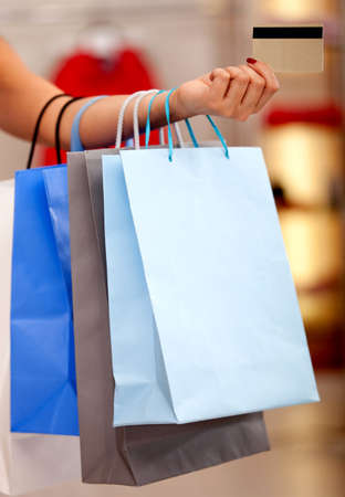 Womans hand holding shopping bags and giving credit card in the mall photo