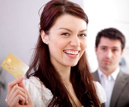businesswoman card: Woman holding a credit card happy with her financial solution
