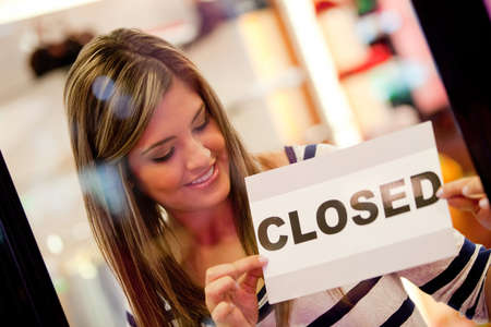 Woman putting a �closed �sign at the door of a retail store  photo