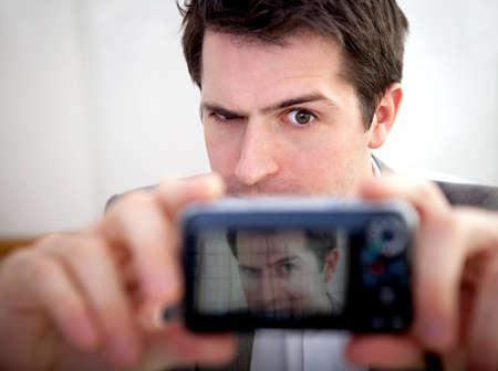 Man taking a self-portrait while making funny faces to the camera  photo