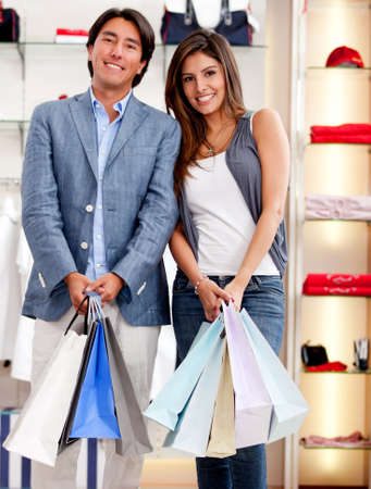Beautiful couple out for shopping holding bags and smiling photo