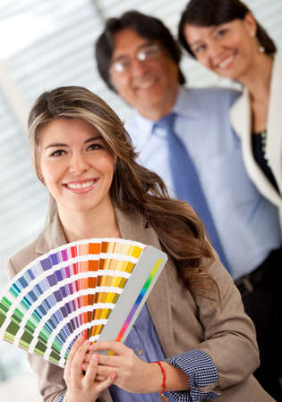 Business couple with an interior designer choosing a color to paint the office  photo