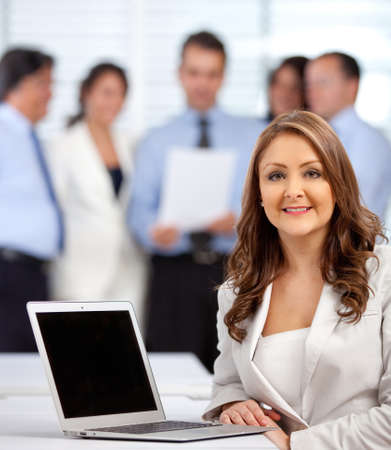 Business woman with a group at the background - indoors  photo