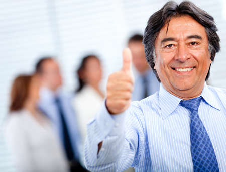 Positive business man with thumbs-up at the office Stock Photo - 11291992