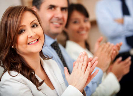 Business woman applauding with a group at the office   photo