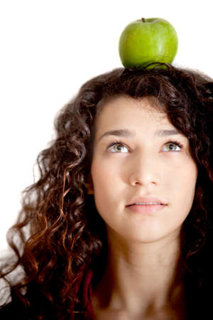 Woman portrait thinking organic with an apple on her head - isolated photo