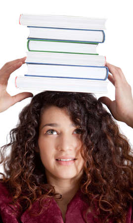 Female student balancing books on top of her head - isolated over a white background  photo