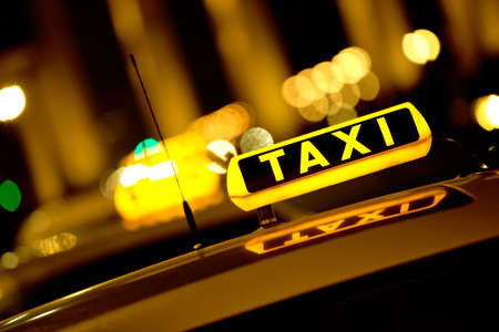 yellow taxi: Taxi cab at night with the sign lit