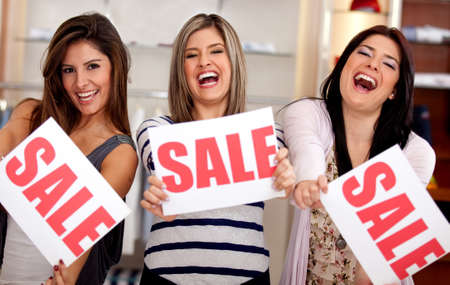 saleswomen: Saleswomen displaying sign of sale at a retail store