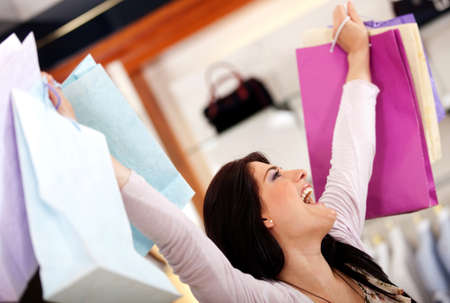 Very happy shopping woman with arms up holding bags photo