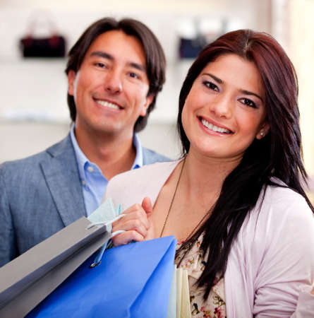 customer relationship: Beautiful shopping couple holding bags and smiling