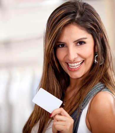 investment solutions: Mujer feliz celebraci�n de una tarjeta de cr�dito o d�bito y sonriente