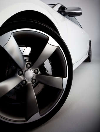 Picture of a white sports carfocusing on the tire  photo