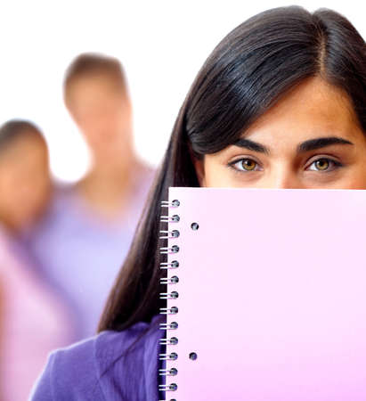 Female student covering her face wih a notebook - isolated over a white background photo