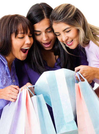 paperbags: Shopping women looking at purchases inside the bags - isolated over a white background Stock Photo