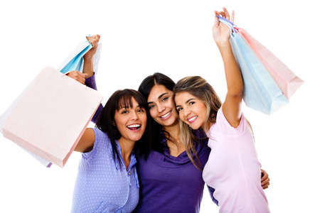 Group of happy shopping women holding bags and smiling - isolated over white  photo